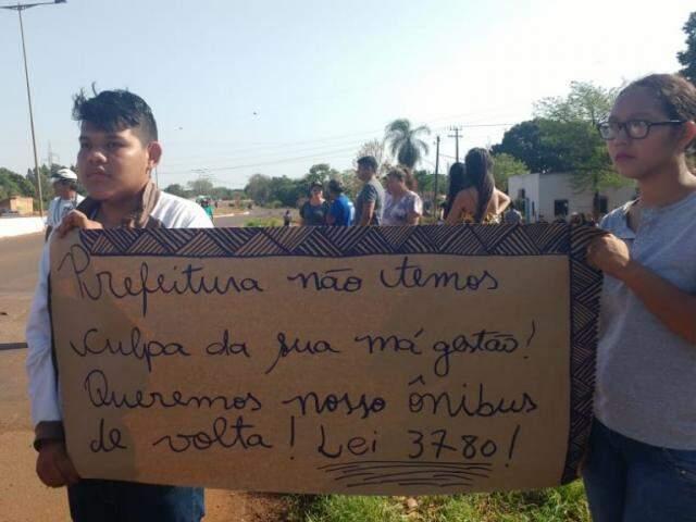 Estudantes indígena com cartaz em protesto contra a prefeitura durante bloqueio da MS-156, nesta manhã (Foto: Adilson Domingos)