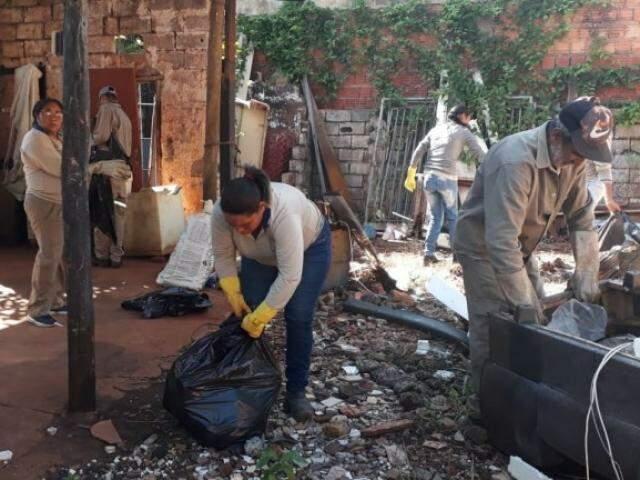 Agentes de saúde de Campo Grande limpam quintal sujo (Foto: PMCG/Divulgação)