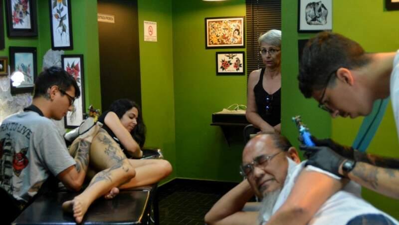 Roberto Higa começando a tatuagem e Sandra, a esposa, ao fundo, morrendo de medo.