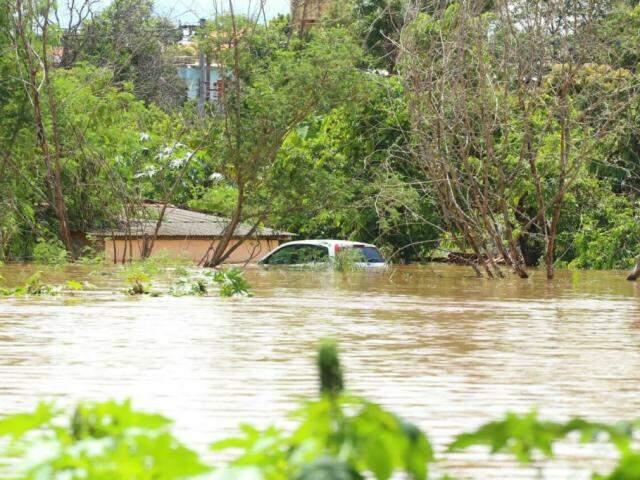 Carro (no fundo) totalmente ilhado na enchente. (Foto: André Bittar/Arquivo).