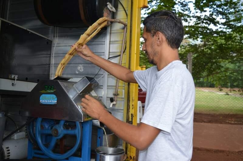 Rogério prepara o caldo de cana, enquanto a mãe vai em casa preparar os salgados. (Foto: Thailla Torres)
