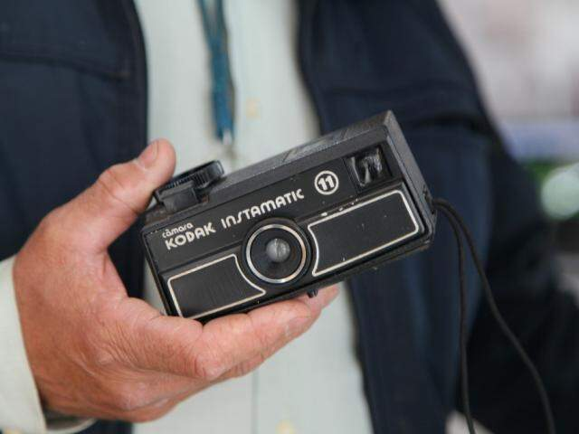 """Ele mostra sua primeira câmera, que comprou logo após a """"desilusão fotográfica"""". (Foto: João Paulo Gonçalves)"""