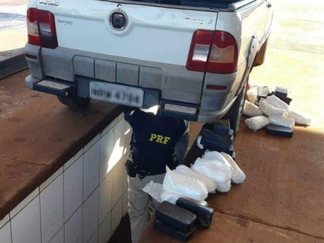 Policial retirando a droga do fundo falso do veículo. (Foto: Divulgação/PRF)