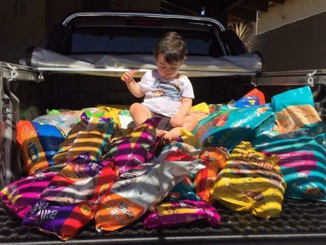 Matheus em cima do resultado da festinha de aniversário: 225kg de ração para cães e gatos. (Foto: Arquivo Pessoal)