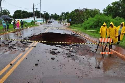 Chuva alaga casas, interdita ruas e abre cratera, que engole carro