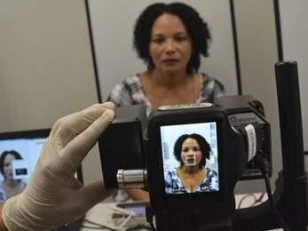 Eleitora sendo fotografada durante cadastramento biométrico; foto e digitais ficam cadastrada em banco de dados (Foto: TRE-MS/Divulgação)