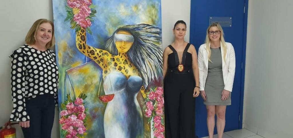 Vera (à esquerda) entregou tela para delegadas da Deam (Delegacia Especializada de Atendimento à Mulher). (Foto: Clayton Neves)