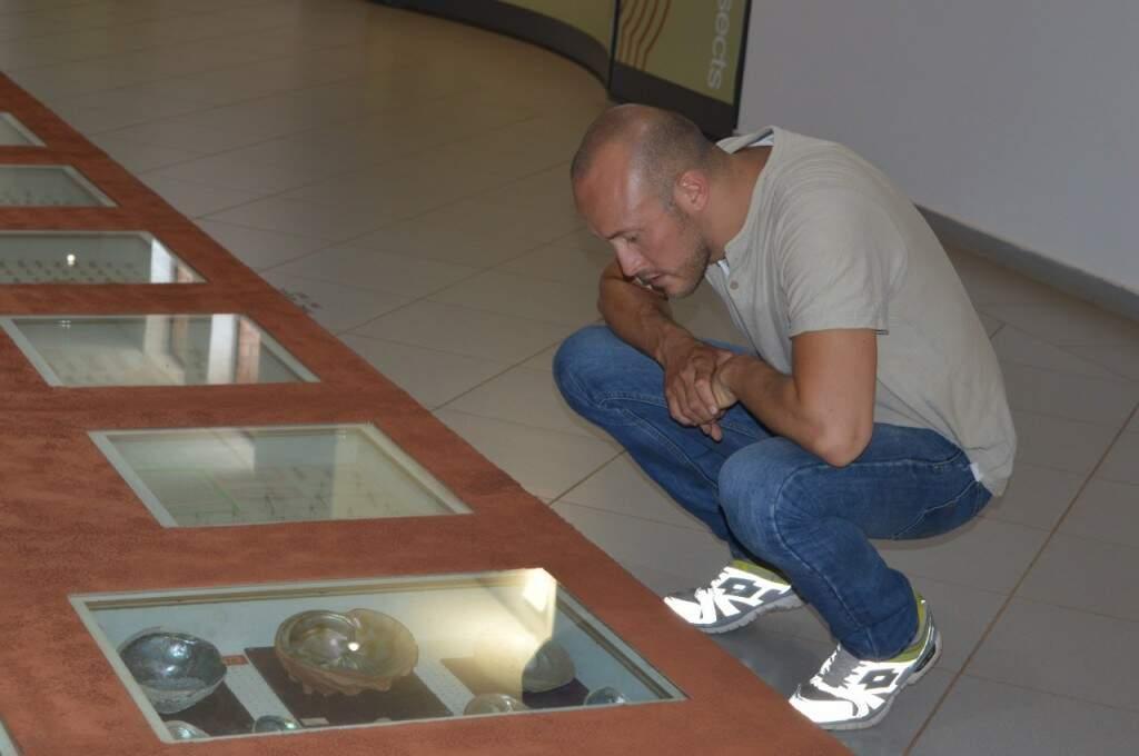 Andres olhando as conchas a mostra no museu (Foto: Alana Portela)