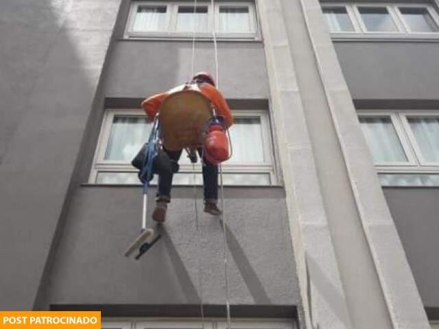Colaborador da TWA realizando a limpeza de janela em prédio com uso de técnica da cadeira suspensa (Foto: Divulgação)
