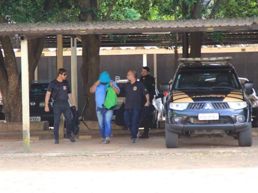 Suspeito esconde o rosto ao chegar à sede da polícia (Foto: Marina Pacheco)