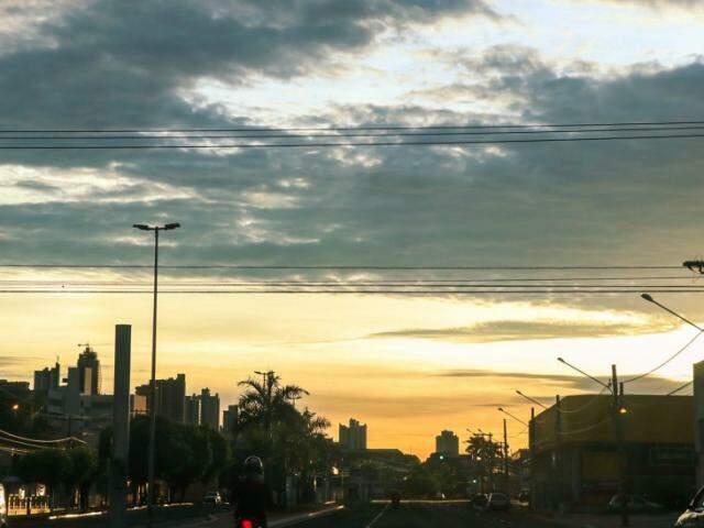 Em Campo Grande, alvorecer foi com céu tomado por muitas nuvens e tons de dourado.  Foto: Henrique Kawaminami)