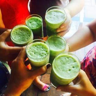 De lanche, suco verde à base de couve, abacaxi, gengibre, salsinha, pepino, cenoura, maçã e longan.