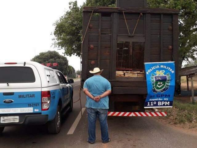 Motorista ao lado do caminhão onde foram encontrados os tabletes da droga. (Foto: Divulgação/PM)