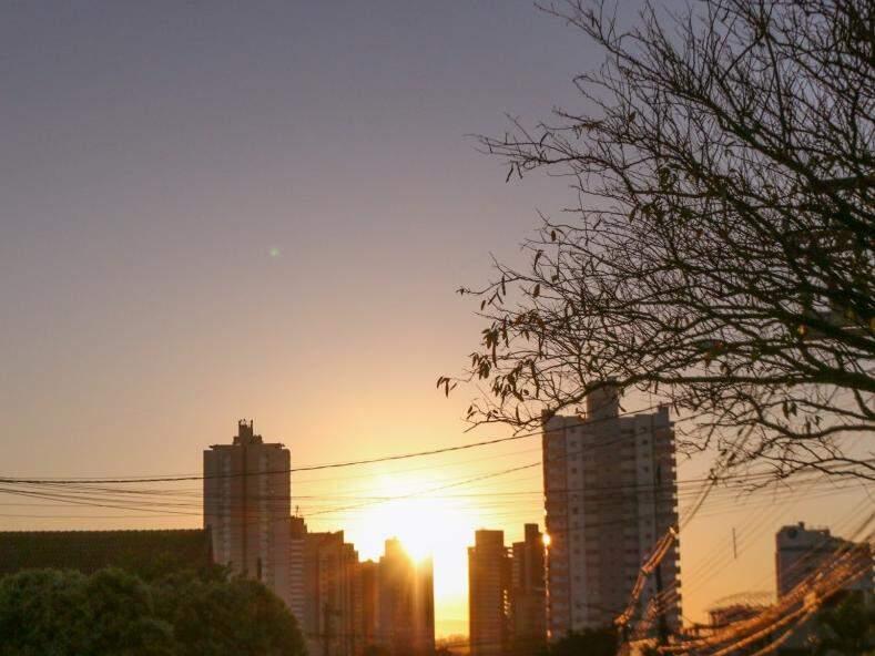 Prédio, galhos secos e sol nascendo compõem cenário na Rua da Paz (Foto: Henrique Kawaminami)