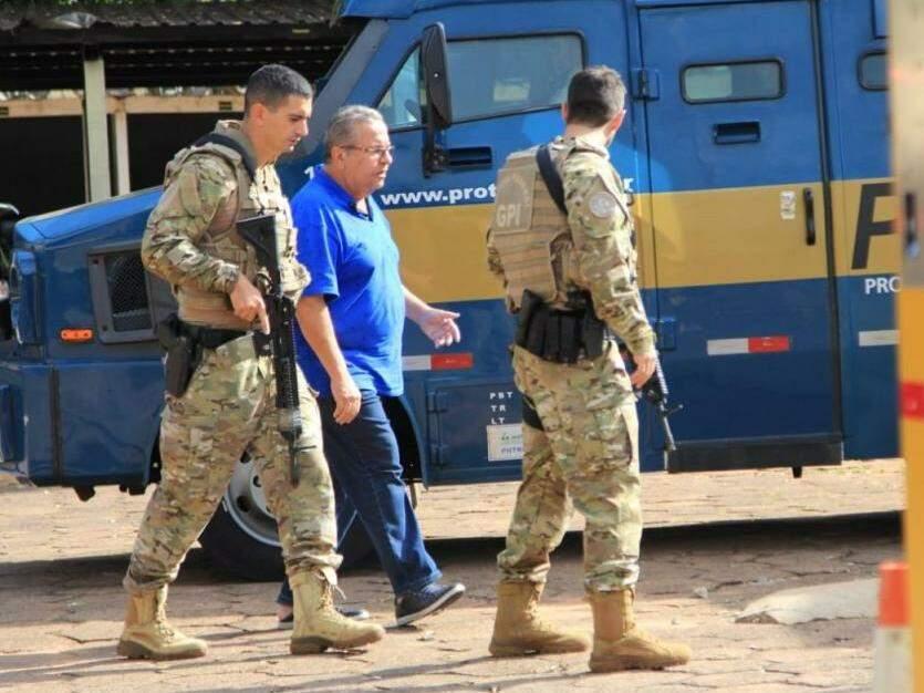 Policiais chegando com um dos suspeitos detidos na operação (Foto: Marina Pacheco)