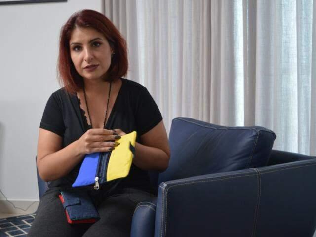 Sabrina mostra as cores das carteiras oferecidas no Crianças e Finanças. (Foto: Thaís Pimenta)