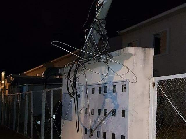 Fios e poste caído sobre a mureta de relógios do condomínio (Foto: Direto das ruas)