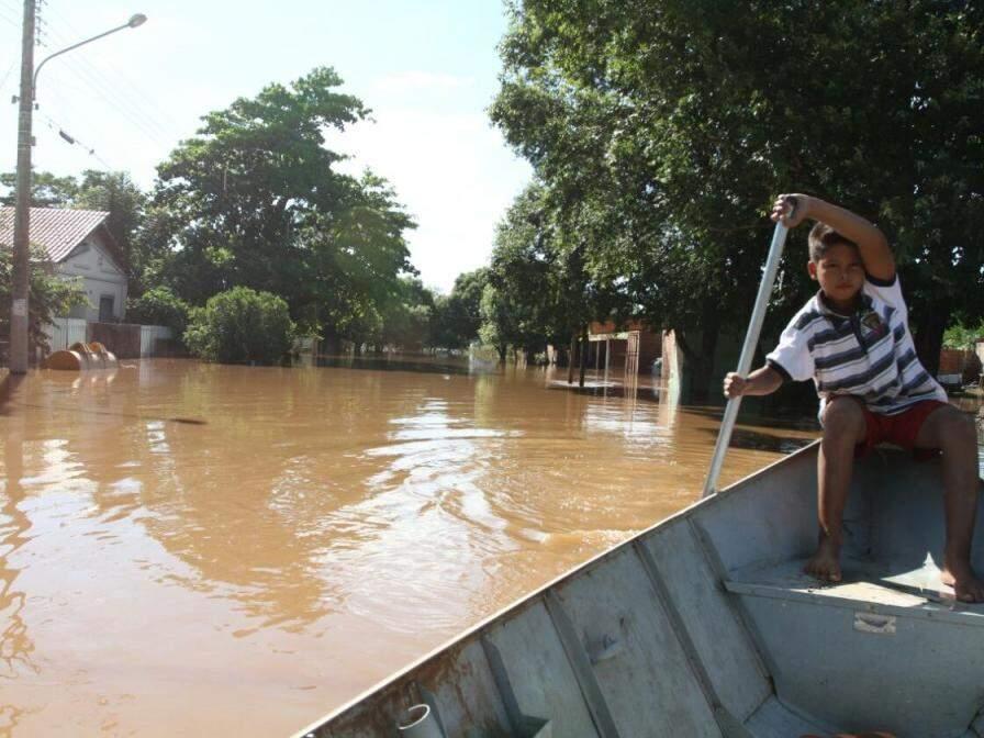 """Criança """"pilota"""" barco pelas ruas de Aquidauana em fevereiro deste ano (Foto: Saul Schramm/Arquivo)"""