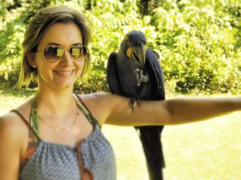 Flavia ao lado de uma arara azul  em MS. (Foto: Arquivo Pessoal)