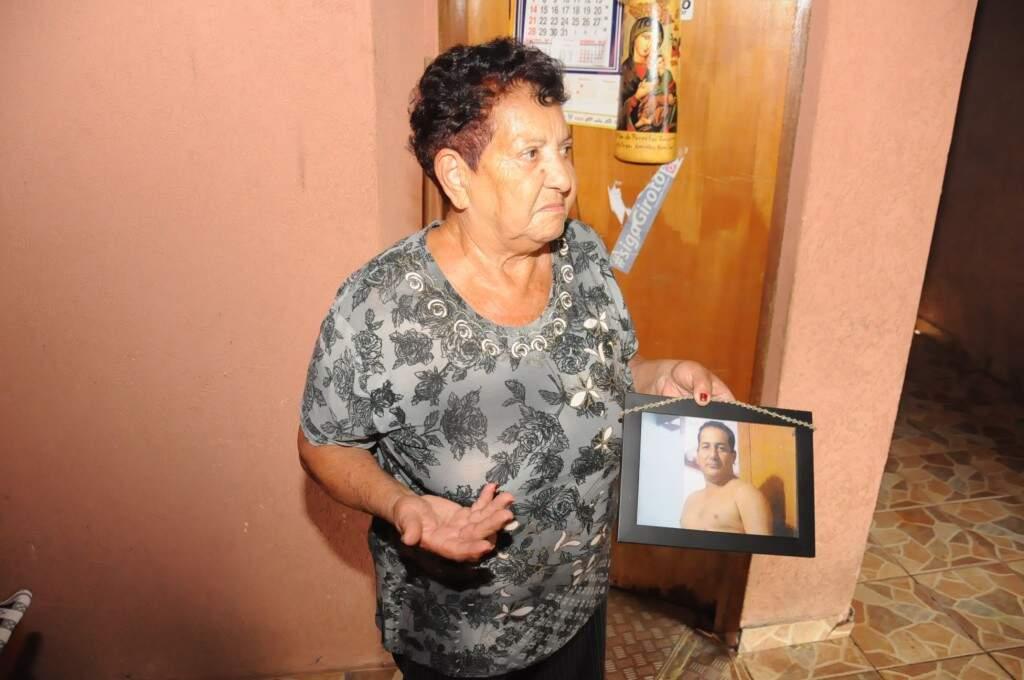 Lúcia conta um pouco do que viveu ali e nos mostra um retrato de seu filho falecido. (Foto: Paulo Francis)