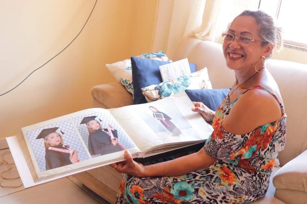 Orgulhosa, Socorro mostra o álbum de fotos da formatura, primeiro passo dado por ela para ajudar a tornar o mundo um lugar melhor