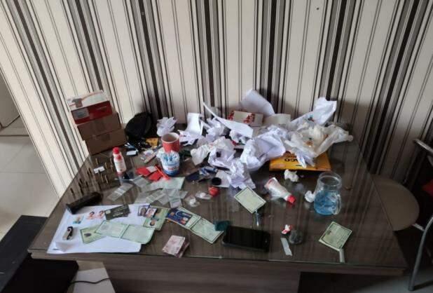 No local onde funcionava a fábrica de documentos falsos, a polícia encontrou documentos, fotos, uma impressora especializada e até arma e munição  (Foto: Gecam)