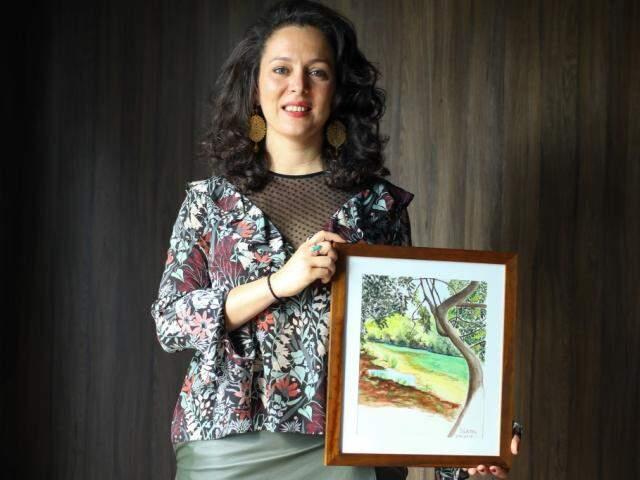 """Diana mostra uma de suas pinturas inspiradas em Bonito, chamada de """"A Fonte"""". (Foto: André Bittar)"""