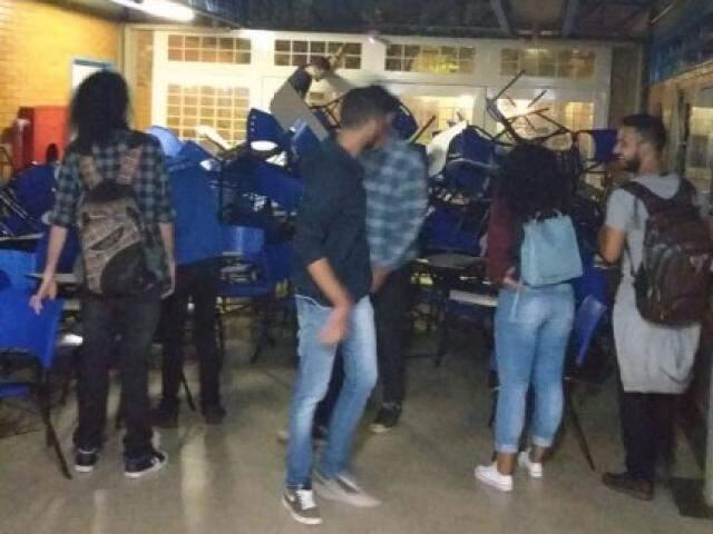 Acadêmicos impedindo passagem por uma das entradas do bloco com cadeiras. (Foto: Direto das Ruas)