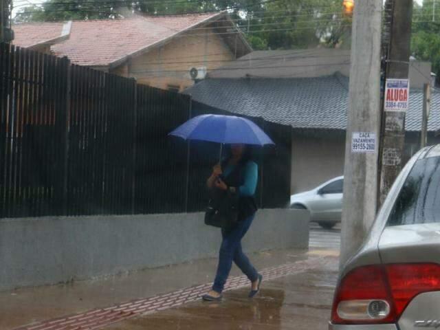 Campo-grandense tentando se proteger da chuva nesta manhã (Foto: Henrique Kawaminami)