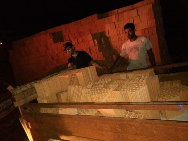 De camiseta preta, suspeito de 27 anos ao lado dao comparsa, de 28, em frente a pilha de tijolos que haviam carregado em carreta. (Foto: Direto das Ruas)