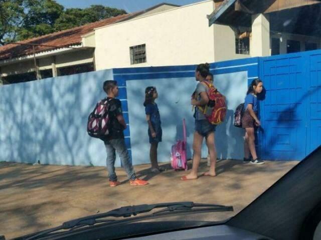 Alunos de uma escola da área central de Dourados esperando abertura de portão às 8h de hoje (Foto: Direto das Ruas)