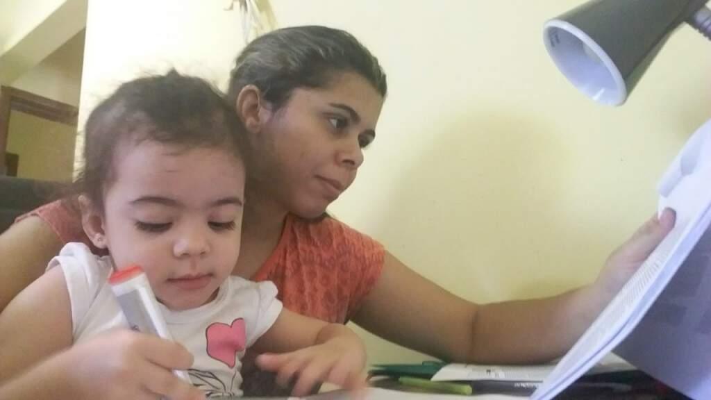 Enquanto mamãe estuda em casa, Mariana brinca com desenho.