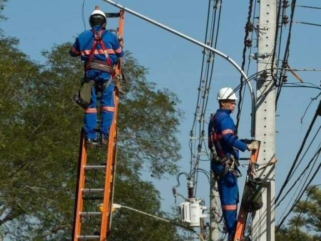Homens trabalham na troca de equipamentos de iluminação na Capital. (Foto: Divulgação/PMCG).