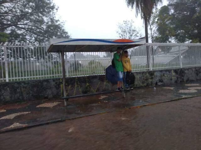 Estudantes tentando se proteger da chuva em ponto de ônibus com rua alagada pela chuva desta tarde (Foto: Geisy Garnes)