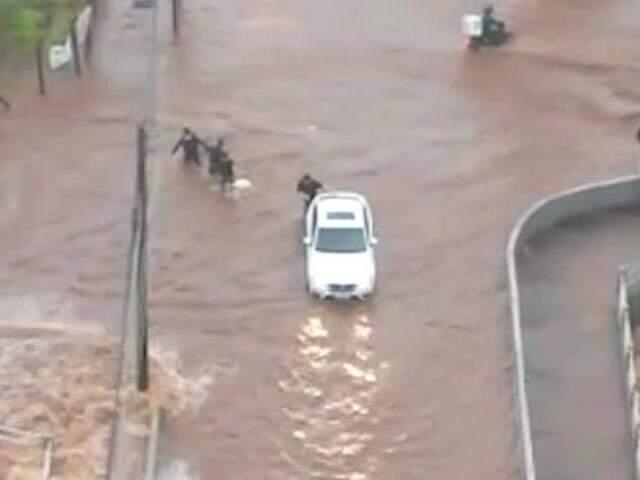 Corrente humana em trecho alagado onde Córrego Prosa transbordou (Foto: Direto das Ruas)