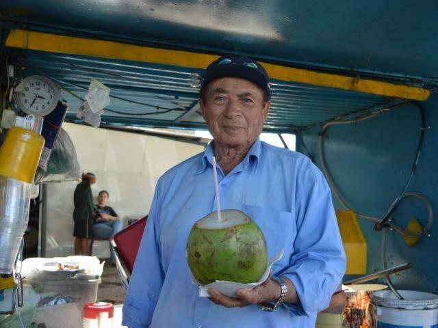 Carlito Barbosa oferece água de coco para as pessoas (Foto: Alana Portela)