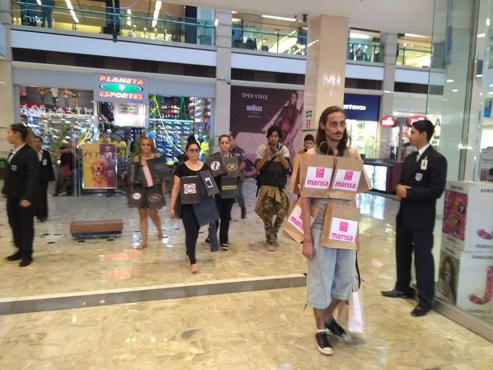 Alunos sendo escoltados por segurança durante a performance, no shopping. (Foto: Reprodução Facebook)