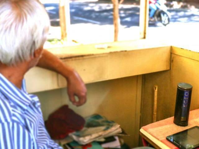 Sentado em sua banca e ouvindo música no rádio, o bicheiro espera pelos clientes (Foto: Henrique Kawaminami)