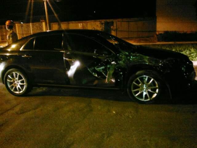 Carro ficou parcialmente destruído após bater em caçamba.