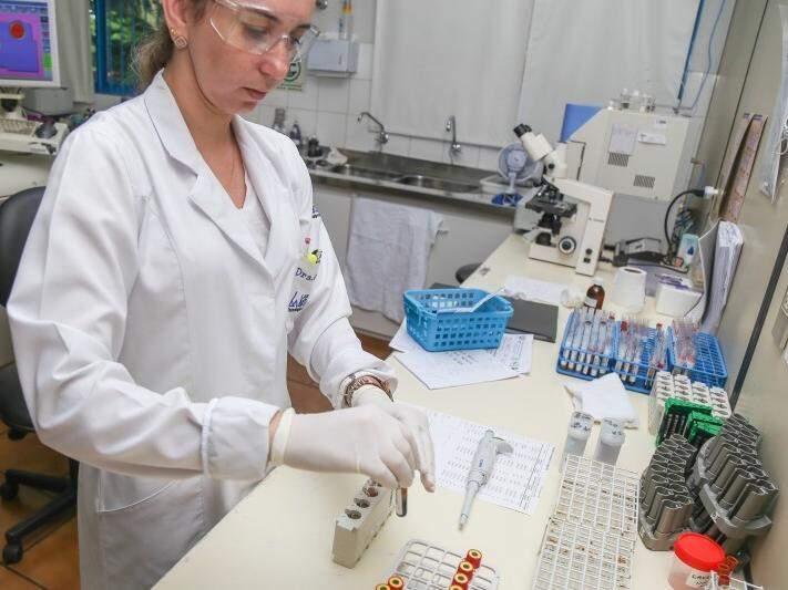Técnica separa tubetes com sangue coletado para exames em laboratório de Campo Grande (Foto: Fernando Antunes/Arquivo)