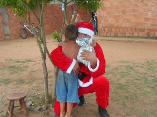 Papai Noel abraça menino antes de entregar presente.