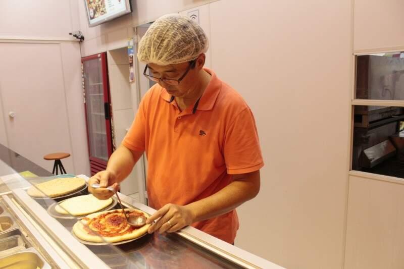 Edson vai montando a pizza conforme o gosto do cliente. (Foto: Thailla Torres)