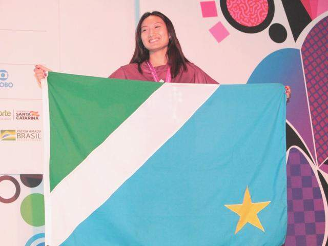 Karoline segura a bandeira de MS no pódio dos Jogos Escolares (Foto: Fundesporte/Divulgação)