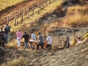 Caixão com corpo de universitário é retirado de local onde jovens foram encontrados.(Foto: Arquivo)