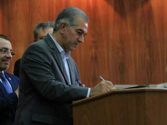 Governador do Estado, Reinaldo Azambuja, assina documento durante solenidade na OAB. (Foto: Marina Pacheco/Arquivo).