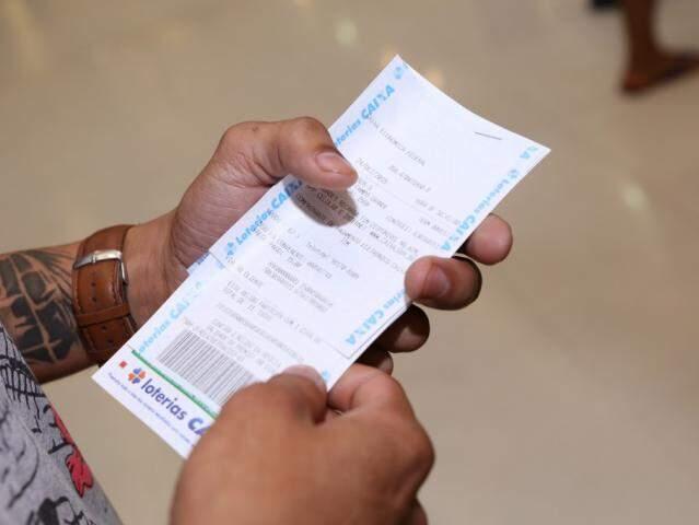 Apostador com cartela da sorte na mão. (Foto: Kisie Ainoã)