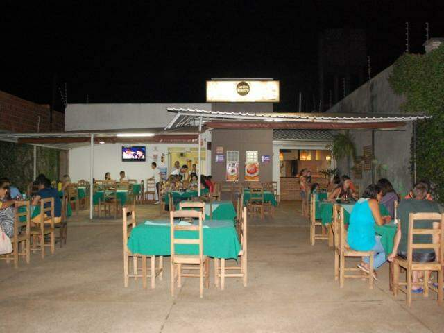 Restaurante é familiar, com mesas de madeira espalhadas por uma varanda agradável.