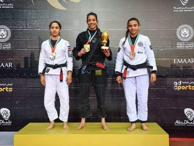 Ariadne Oliveira, ao centro, segura medalha e troféu conquistado em Abu Dhabi (Foto: Divulgação)