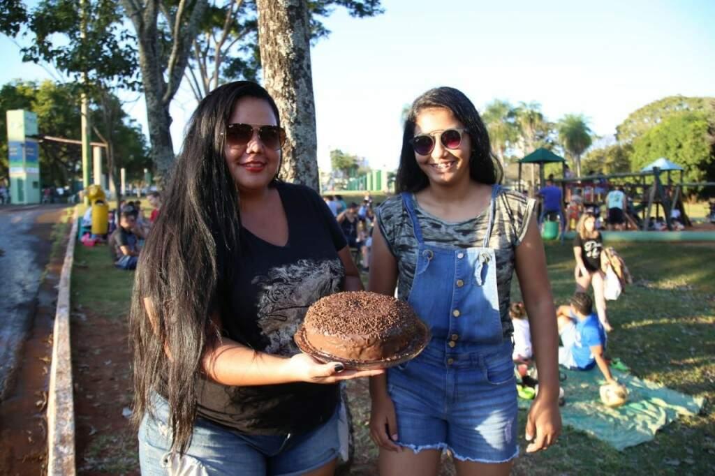 Mariana Machado segurando o bolo de chocolate para o piquenique com a irmã, Giovanna (Foto: Alana Portela)
