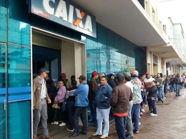 Trabalhadores fazem fila na porta de agência da Caixa em Campo Grande em dia de saque extra do FGTS. (Foto: Arquivo)